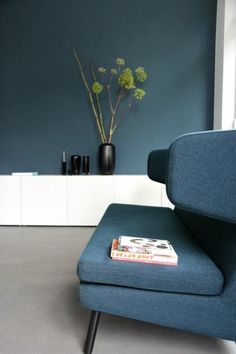 fauteuil bleu dans le salon chic, sol en lino gris, murs bleus foncés