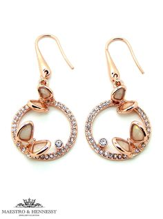Mother of Pearl butterflies sitting atop a crystal pave rose gold plated circle on a French hoop earring. Rose gold plated butterflies with white mother of pearl inlay. Large white crystal set in rose gold offsets the design with playful butterflies on a garden of crystals. This stunning piece is part of a mother of pearl butterfly rose gold plated earrings collection with a matching necklace and ring.