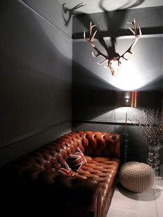 tufted leather sofa in loft living room with charcoal grey walls and deer antlers