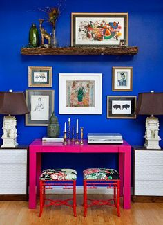 royal blue wall. pink table. fancy stools. wall hangings.