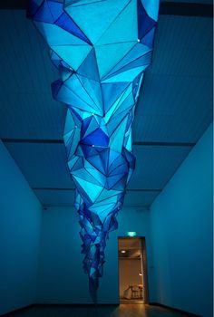 "Artist: Gabby O'Connor, ""What Lies Beneath"" is the result of an aesthetic research into what the artist believes Antarctica is like. The installation is made up of thousands of small paper triangles dyed in shades of blue-green, and then stapled together in 2011. It was just about dream and imagination."