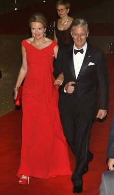 Reina Matilde de Bélgica Acto: Viaje oficial a Polonia. Fecha: 14 de octubre de 2015. 'Look': Matilde de Bélgica se decantó por un elegante vestido en color rojo. Como complementos escogió zapatos peep toes y cartera, ambos al tono.