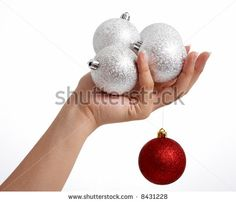 a hand holding some christmas tree decor - stock photo