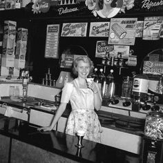 A young woman working behind the counter at a classic soda fountain. #vintage #1940s `