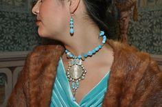 Authentic HUngarian coin folk jewellry redesign necklace, earrings. Antique Maria Theresia coin is framed in silver with little turqouise gemstones.The necklace is made of blue vintage glass and silver beads./ Rábaközi lázsiás, nyakék, fülbevaló redesign. A medál: Mária Terézia antik pénzérme ezüstbe foglalva, tetején apró türkiz drágakövek. A nyakék kék vintage gyöngyökből és ezüst gyöngyökből fűzve.