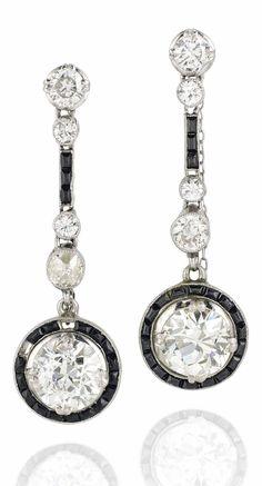 A PAIR ART DECO ONYX AND DIAMOND EAR PENDANTS, CIRCA 1925. Each composed of an old-cut diamond drop within a calibré-cut onyx border suspended from a similarly-set diamond and onyx line and single-stone diamond surmount, 3.9cm. #ArtDeco