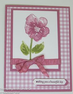 """Image of the completed card front displaying a pink flower with green stem and leaves; pink ribbon and three layers of card stock, as well as the sentiment, """"wishing you a beautiful day."""""""