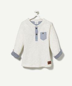 LE TEE-SHIRT AMBITION :                     Un tee-shirt super stylé pour un look dandy et classe ! On craque pour les coudières et le col tunisien !            LE TEE-SHIRT AVEC COUDIÈRES, col tunisien fermé, manches longues avec bouton pour faire tenir le revers imprimé rayé, fermeture par boutons sur le devant, 1 poche, patch faux cuir, chiné.