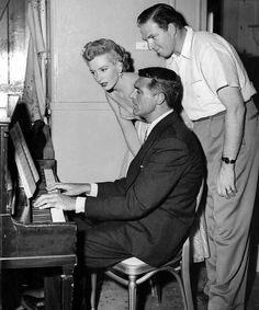 "On a break from filming ""Dream Wife"", Deborah Kerr and writer-director Sidney Sheldon delight in Cary Grant's musical ability"