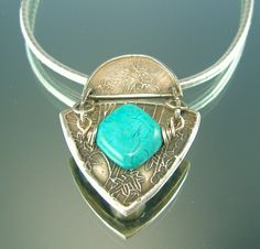 Turquoise Shield -  This unusual pendant is an attempt on my part to bring together my new love of metal clay with my old faithful wiring skills. To wire the stone over the silver shield gives it some dimension and unexpected depth. I am still not sure exactly how I want to handle this. It is definitely a work in progress but I do think that this one is closer to where I am heading. It has an earthy appeal, strong yet not overbearing.