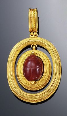 GOLD AND CARNELIAN PENDANT, ROBERT PHILLIPS, 1870S. In the archaeological revival style set to the centre with an oval carved carnelian scarab within a rope work surround suspended within a similar larger outer frame, maker's mark for Robert Phillips, fitted case by Phillips, 23 Cockspur Street, London.
