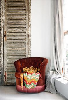 I love the opulence and richness of the chair set agains the simplicity of the draped curtain and rustic shutter door leaning against the wall.  What a contrast!