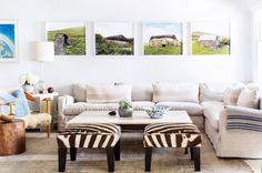 Living room with zebra stools and art above sofa.