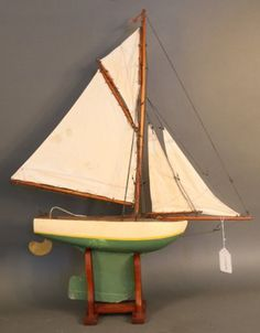 Pond yacht with painted hull set on a wood cradle