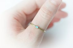 This is a unique brass and american turquoise ring made in my studio. The turquoise is a small raw chip turquoise, rectangle shapet. It is part of a larger piece of american blue turquoise. It is light blue. It is set in a really thin and minimalistic band of solid golden colour brass. There is patina and hammering on the brass. Stone size: 2 x 4 mm. Ring size: 7 3/4-8 I can hammer it up to 8 1/4, let me know if you want me to at checkout. I am able to make similar rings (with aprox...