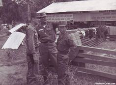 MAAG Advisors Lt. Colonel John Brooks and Major Chester Peterson discuss Strategic Hamlet construction with province chief Major Tran Van Minh.    Photo taken: Ben Cat (III Corps) 21st July 1962