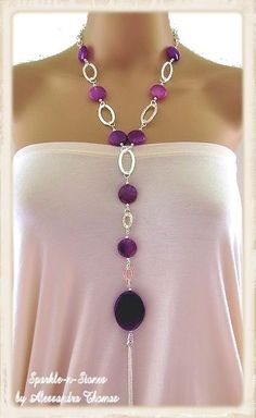 "The Bella Necklace - Make a fashion statement with this bold yet slimming amethyst agate necklace. Rich, deep tones of purple fire agate stones form a ""y"", leading down to a substantial sized amethyst agate oval which has a 5"" tassel dangling from it for movement.  Stunning!"