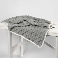 A small blanket crocheted in a pattern of diagonal bobbles (also called popcorn stitches) and finished with a scalloped edge border. Print the pattern which is available as a separate PDF file for this idea. Bonnet Crochet, Crochet Diy, Crochet Home, Small Blankets, Knitted Blankets, Baby Afghans, Baby Blanket Crochet, Popcorn Stitch, Pom Poms