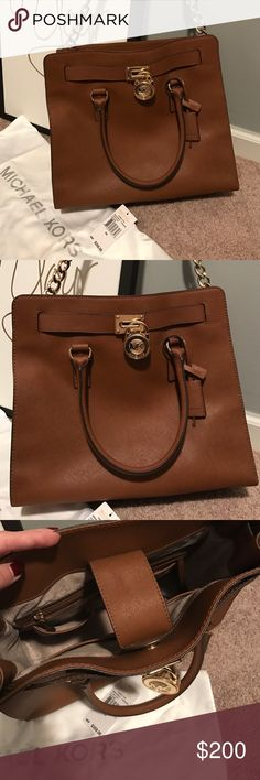 Michael Kors Hamilton LG Leather Tote In Luggage Michael Kors Hamilton LG Leather Tote In Luggage. The bag has a small water stain on the inside flap pictured above. Otherwise mint condition. Saffiano Leather in luggage color. Comes with bag cover and original tag. No trades. Michael Kors Bags Totes