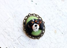 If you love your furry friend and you would love to have him always with you, I can make an unique jewelry to have and cherish all the time when your pet friend isnt around you. ------------------------------------ This is a handmade custom portrait brooch, made entirely by me out of polymer clay. It isnt painted, which makes it more difficult to create, but the look is more realistic. The cabochon is nestled in a bronze tone base. I started the work from a couple of Dantes pictures and his…