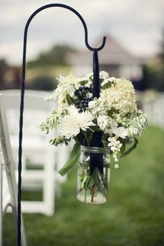 Mason jar bouquets along the aisle.
