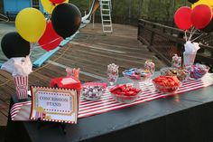 """The concession table for H's movie party. I used clear glass bowls & glasses to display the candy. I used popcorn bags for the goody bags that the kids got to fill. The popcorn """"bags"""" that the balloons are attached to are hard plastic and came from the local dollar store. Standard plastic tablecloth and the red and white runner is wrapping paper."""