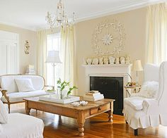 White takes a creamy approach in this living room that mimics the look of soft candlelight to create a vintage look. The yellow-white walls soften the crisp white on the trim and furniture. McCoy pottery and a metal piece add