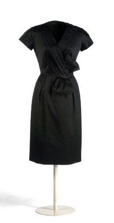 Vestido de raso de seda negro ajustado al talle con manga japonesa muy corta. Va cruzado en pico y con delantero drapeado que se recoge en lazo en el lateral izquierdo. La falda se ajusta a la cintura con tablones y se cierra en la espalda con cremallera.  Christian Dior