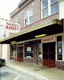 "Smitty's Market (The once and former Kreuz Market underwent a name change in 1999 when Nina Schmidt Sells — daughter of Edgar ""Smitty"" Schmidt — allowed her brother Rick to take the original Kreuz name (and some of its coals, from a fire which is said to never die) and open a ""new"" Kreuz Market down the street. Smitty's still occupies the same century-old store in which Charles Kreuz first began smoking meat in 1900. Cash or check) Lockhart"