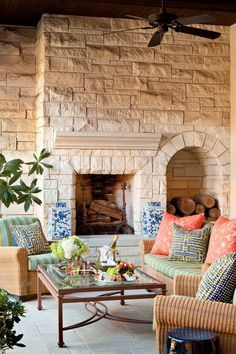 Spanish Revial Redo - Decorating a High Definition Dallas Home - Southernliving. Vivid outdoor cushions add punch to the creamy tones of wicker and limestone on the porch.  Read More About This Dallas Home Love It? Get It!