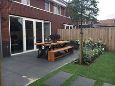 Kindvriendelijke tuin met kunstgras en grote tegels