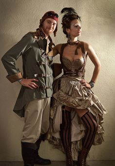 Steampunk Couple, Muted Color Palette - The man is dressed as a Steampunk Pilot, the woman is dressed as a Steampunk Showgirl. Color palette: taupe, olive green, khaki  - For costume tutorials, clothing guide, fashion inspiration photo gallery, calendar of Steampunk events, & more, visit SteampunkFashionGuide.com