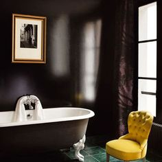 The rich composition of warm colours in their deepest hues, a classic claw foot soaking tub and a single yellow Renaissance-style chair give this bathroom an elegant appeal. The mood is luxurious without being decadent, as there are few amenities or accessories.