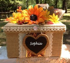 An orange sunflower tops this rustic burlap covered keepsake box and is perfect for a fall wedding. Thank your bridesmaids with this personalized memento of your wedding using this box alone or holdin
