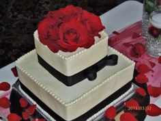 2-tier square red & black wedding cake.  Frosted in buttercream, black ribbon w/ simple bow, and fresh red roses on top tier~