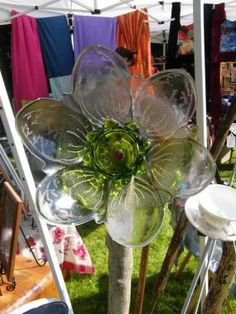 Repurposed/Recycle.   flowers made out of glass bowls, candle holders, ashtrays, plates, knobs, tins anything that can transform into a flower.  then drill holes in them with a diamond bit (use water), attach them to driftwood with bolts (insert rebar to the bottom of the driftwood) or attched them onto copper pipes and conduit..