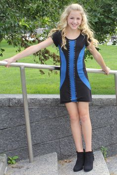 Chloe Lukasiak from dance moms wearing a Sally Miller dress. A black background with two blue curves around the edges and a blue stripe down the middle of the dress with short black sleeves