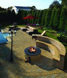 Feuerstelle mit gemauerter Sitzbank neben dem Schwimmbecken im Garten