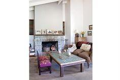 En el living, el sofá tapizado en pana marrón cobra color con aguayos antiguos apoyados en el respaldo, una manta tejida y un almohadón de piel de oveja (Prágmata). Sillitas norteñas con asiento bordado (Ana y Malena López Sanabria)..