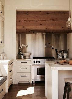 Ken Linsteadt Wood Kitchen Hood Remodelista: reclaimed wood face on range hood in a creamy white kitchen w/stainless steel backsplash Modern Farmhouse Kitchens, Country Kitchen, New Kitchen, Home Kitchens, Kitchen Dining, Wooden Kitchen, Rustic Kitchen, Petite Kitchen, Neutral Kitchen