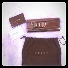 """Authentic Gucci clutch wallet Authentic gold metallic 100% genuine leather Gucci clutch wallet . Gorgeous belt buckle design! Inside pristine condition. Front in excellent condition! Minor scratch on back- shown in photo-, not bad but discounting generously! Measures Length 9 x3.5Wx 3"""" Depth. One button magnetic closure. Overall great condition, lightly used. Discounting generously!! Gucci Bags Clutches & Wristlets"""