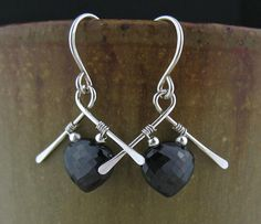 Short black spinel wire wrapped stone earrings - these are high quality stones, well cut and faceted. They show an elegant glitter as they move about in the light, presenting a classy contrast with the silver. I hammered the frame for a flattened texture, then wrapped the stones to