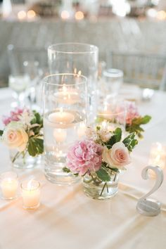 Table decor with candles and mini posies in what looks like tumblers. What fun to fill barware with flowers and then present as a gift to the bride after the wedding.