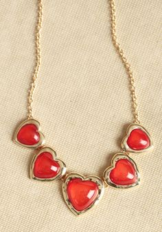 Love Is In The Air Necklace 18.99 at shopruche.com. Five heart pendants with shimmery red centers adorn this gold-toned necklace for a darling statement look.18