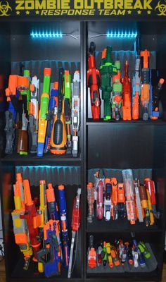 """We made this Nerf gun cabinet with 2 IKEA Besta shelf frames. The gun """"holders"""" are acoustic foam tiles, cut to fit and the shelves are lined with thick, tool box drawer liners (to prevent the guns from slipping and scratching the wood) The color-changing lights are IKEA DIODER. We had the sticker custom made and then mounted it on IKEA's Mosslanda picture ledge. There are screw holes to attach the Mosslanda to the Besta shelf units."""