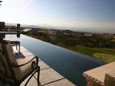 This lap pool features an infinity edge and dark pebble interior. The absence of fencing, landscaping or other structures on this backyard hillside allows for an uninterrupted vista of the valley.