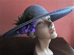 Authentic vintage 1980s wide brimmed sun hat. Top quality from Frank Olive. Spray of purple violets tucked under the brim with green stems and leaves on top. I,ve never seen this amazing color. Concentrically sewn straw in denim blue/gray/tobacco, looks like the distressed, faded dirty (good dirty) denim jean. Wide sun shielding wire edge brim and low rounded crown. Elastic band to secure.  Condition: Very very good vintage condition, slight wear inside band, First 3 photots are cor...