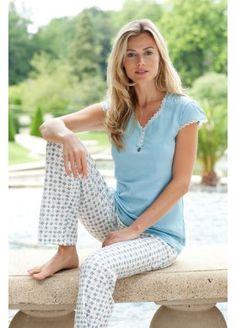 Een leuke pyjama uit de serie Pastunette Deluxe. De lange pyjamabroek heeft een fijn patroon. Het pyjamashirt is licht blauw van kleur. De mouwen en de hals zijn afgewerkt met wit kant. Onder de hals zitten knoopjes en een strikje.