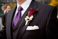 BAM!!!  This is EXACTLY what I envisioned for a red and purple wedding: simple, refined, elegant and still combining both colours.   The groom's pinstripe tuxedo with purple paisley tie and deep red calla lily boutonniere.