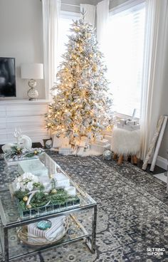 White Flocked Christmas Tree in a transitional style home. See the decorating tips to get this look! See the sources for the coffee table, area rug, lamp, flocked tree, Mongolian fur stool and the gray wall paint color in the blog post.